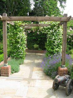 Garden by Surrey garden designer Linda Regel. The pergola is planted with roses, evergreen jasmine Trachelospermum jasminoides, and lavender, to provide a scented walkway.