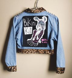 This cropped denim jacket has soft plush leopard trim at the collar, waist and sleeves. It has a hand painted Bikini Kill back patch and a pink
