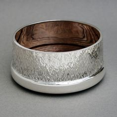 Silver wine coaster with flame texture and mahogany base