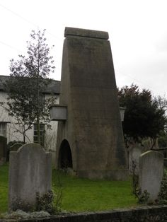 """A tomb, in the shape of a tower, is to be seen in the churchyard. Now overgrown, it is a picturesque object, but the peculiarity of it is that the body of the person """"buried"""" here a certain William London, in 1809 is contained in a stone-encased coffin, projecting from the tower, half-way up. Legends tell that the descendants of William London, a Scotch merchant, retain the property bequeathed by him so long as he remains """"above ground."""""""