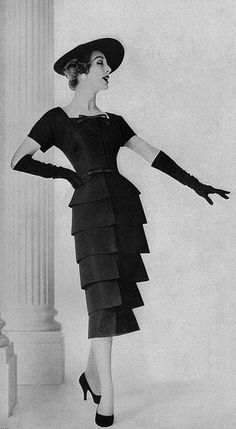 1950's vintage fashion. Black ruffled dress with matching hat and gloves!