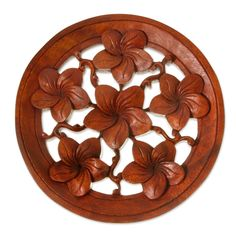 Frangipani blooms on a circular medallion, each detail hand-carved from suar wood in this stunning relief panel. By Seji Taram, the six lovely flowers on this wall sculpture are a constant reminder of Bali's natural beauty.
