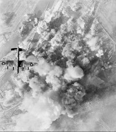 An Avro Lancaster of No. 300 Polish Bomber Squadron RAF flying over the smoke-covered target area during a daylight attack on the oil refinery and storage depot of Deutsche Vacuum AG at Bremen, Germany, by 133 Lancasters of No. 1 Group and 6 De Havilland Mosquitos of No. 8 Group.