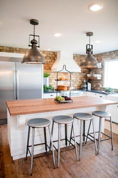 The kitchen in the King home has been completely transformed and repositioned. Some of the key elements of the kitchen are the open shelves, the black granite countertops, the brick backsplash, a vent hood, stainless steel appliances, industrial light fixtures and a custom island, as seen on Fixer Upper.