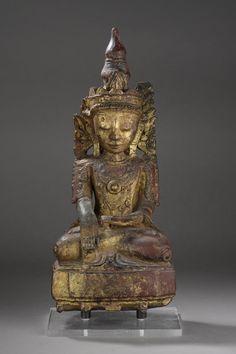 Buddha Maravijaya assis en méditation richement vêtu et paré d'un diadème à ailette latérale surmonté d'un haut rasmi. Bois laqué et doré. Birmanie. Royaume des Etats Shan. 17 ème siècle. Ht 43cm x 21 x 13cm.