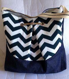Bolsa saco em jeans, estruturada e forrada, alça em tira de algodão com bordado. Com fecho magnético..