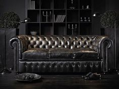 Luxury black leather Chesterfield sofa in dark living room