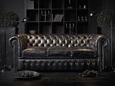 Luxury black leather Chesterfield sofa in dark living room
