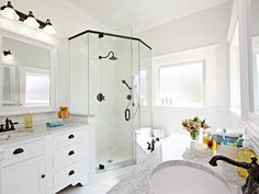 A light-filled master bath, with a glass-enclosed shower and large mirrors feels expansive
