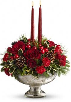 Two deep red taper candles are secured in a bed of noble fir, white pine, variegated holly, red roses and red carnations. pinecones and berries add more seasonal color.