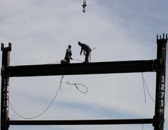 Ironworkers Jim Brady, left, and Billy Geoghan release a steel cable after connecting a steel beam between two columns at the top of One World Trade Center to make it New York City's tallest skyscraper, April 30, 2012 in New York. See: http://su.pr/1jzzDU