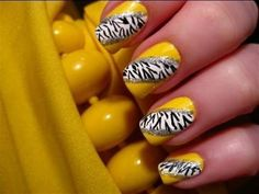 Animal print inspired yellow themed nail art design. Using yellow as the base color, the animal prints are painted on top with help of a white frame to make them look more noticeable from afar.