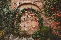 Wedding ceremony arch of ivy with hanging red and blush flower blooms by Wild Green Yonder