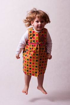Dress without sleeves. Pattern with big, color dots and with flower motif on the front. Zip fastening at back.