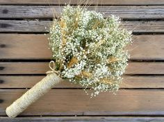 A simple bridesmaid bouquet of summer harvested wheat and dried babys breath with the option of additional flowers and wrap styles. You can choose this bouquet in an up-cycled coffee bag burlap wrap tied with sisal, burlap twine, satin ribbon in a choice of colors or in an all sisal twine or satin wrap in a choice of colors. This all natural dried bouquet was inspired by future brides and will make a wonderful keepsake after the wedding.  Approximate Measurements: 13 high with a 5- 6 handle…