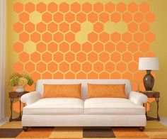 This is a creative interior wall design that mimics a honey comb pattern. The bright pattern has visually appealing positive and negative spacing, and the color choice compliments the furniture as well.