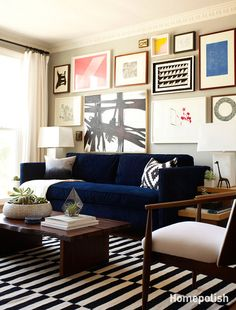 Love the navy couch, the graphic rug, the coffee table, the art, all of it