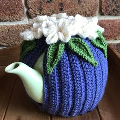 Violet pure Australian wool tea cosy with crocheted white flowers and green leaves by alittlebirdmademe on Etsy https://www.etsy.com/au/listing/581086296/violet-pure-australian-wool-tea-cosy