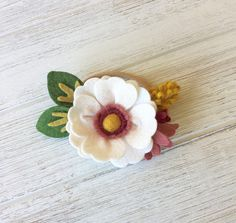 This adorable daisy headband is the perfect accessory for the spring! It is handmade with wool blend felt and attached to a nylon headband. The super soft and stretchy headband will comfortably fit newborns - teens. The entire length of the bloom and leaves arrangement measures