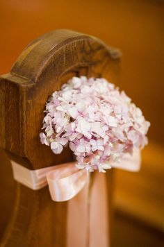 A pink satin ribbon and single hydrangea make a sweet addition to this church pew.