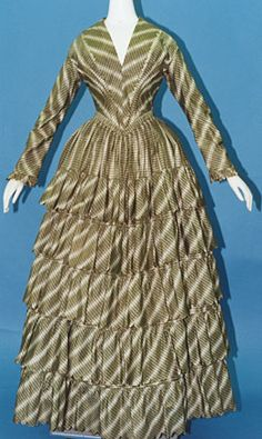 Day Dress, c1850, Green and white plaid silk taffeta; worn over crinoline; skirt with five flounces with scalloped edges.