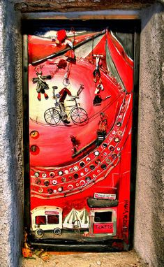 Valloria,-Italy - Art is splashed all over the village doors in Valloria, Italy. Where this bright red door shows off the fun of going to the circus.