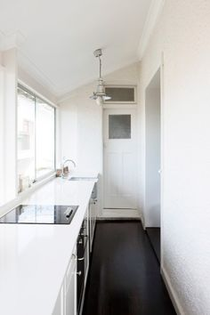 sleek galley kitchen. make a small kitchen seem less cramped with white and no upper cabinets