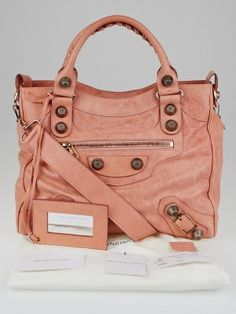 "This beautiful Balenciaga Vieux Rose Lambskin Leather Velo Bag from has a chic shape that is made of distressed lambskin leather in lovely pale pink lambskin with gorgeous goldtone ""Giant 21"" hardware that creates a lovely color combination. It also has a detachable shoulder strap for those non-toting days and a matching mirror. A great bag for any stylish fashionista on-the-go. Giant 21 hardware is now discontinued and has been replaced with miniature ""Giant 12"" hardware, so don't"