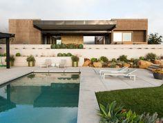 une maison de vacances au design contemporain, couloir de nage relaxant et entourage piscine en dallage de pierre