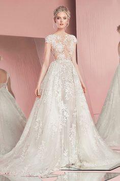 This wedding dress featured jewel neckline, cap sleeves and lace embroidery sheath wedding dress with overskirt. Zuhair Murad, Spring 2016