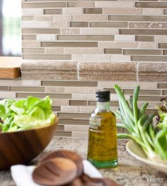 A smart mix of stone and glass tiles form a stylish backsplash with natural texture. Choose sheets of linear glass tile with assorted sizes and a random pattern for visual variety, or opt for aligned tiles for a streamlined look.