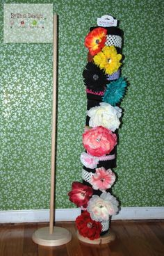 Just made this Headband Display Holder to put on the table for the craft shows.  It's very easy to make.  All you need is a Wooden Base and a Wooden Dowel which you can find in any craft store.  Use a large screw and drill the screw in the center of the base while attaching the dowel.  Make sure you get a dowel this enough so that it doesnt crack when you put the screw in.  Then wrap 3 paper towel rolls with any fabric of your choice and slide through the dowel.  And there is your display.