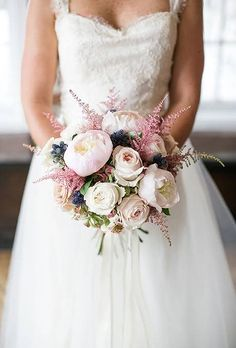 a perfect bridal bouquet of blush peonies, white roses, astilbe, and thistle, for a look that feels fresh yet still classic | 44 Fresh Peony Wedding Bouquet Ideas : Brides.com