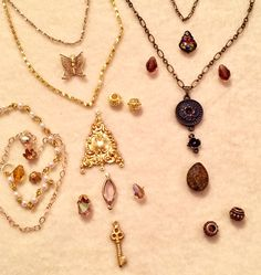 Work Table Wednesday 2/7/18 - Designing necklaces to layer.   B'Sue Boutiques Classic Gold finish brass connector, key charm and flower bead cap.  B'Sue by 1928 Rusty Iron finish flower connectors.   Swarovski crystal beads and  vintage peacock finish fancy pendant. Bronzite stone teardrop pendant. Chains except gold necklace chains from B'Sue Boutiques; vintage chains and crystal connector.