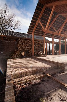 Het voorhof in de oksel is een beschutte plaats geworden met links een border voor leifruit. Tegen de wand staat het haardhout opgestapeld.