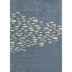 This playful hand-tufted area rug showcases a contemporary design and cool-toned coastal hues. A school of white, seafoam, and yellow-green fish swim whimsically on a deep blue wool and viscose backdrop.