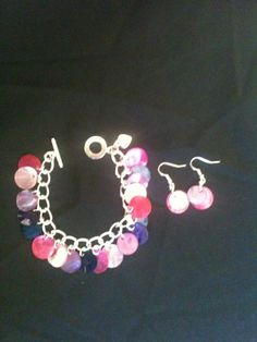 Pink and Purple Shell Button Charm Bracelet with Matching Fish Hook Earrings. Handcrafted using a silver plated chain. Measures 7 1/2 inches and fastens with a toggle and clasp. £7.00