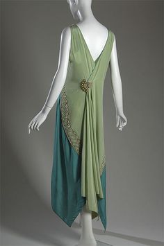 Green silk charmeuse evening gown with metallic thread embroidery and pearl beadwork (back), by Callot Soeurs, French (c. 1928).  I love the two shades of green used! Gown is sleeveless, with handkerchief hemline.  The fanned beaded clasp, at the back of the gown, attaches off center below the deep v-neckline.  It creates a lovely 'fall' down the back of the gown.