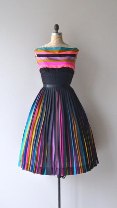 Vintage 1950s silk blend dress with bright stripes paired with black, wide neckline, narrow panel seamed waist fitted at the natural waist, full