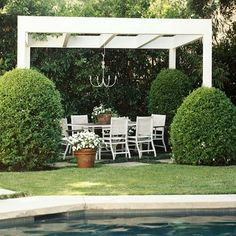 Виниловая белая беседка с зоной отдыха у бассейна, которую защищает и подчеркивает зелень вокруг.