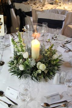 Flower Design Events: Hurricane lamp surrounded by spring flowers at Samlesbury Hall.