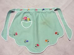 Scattered embroidered flowers and bias-tape trim enhance this charming little vintage half-apron. I love the gentle scalloped hemline and especially the pocket! :)