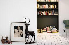 Partly hidden bookshelf with black wall and shelfs.Dos Family/hometours/ Sara + Kristian