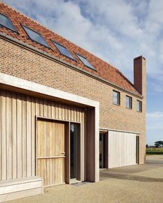 This house in rural England was designed by British architect Lucy Marston to reference old English farmhouses and features red brickwork, a steep gabled profile and a corner chimney