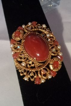 Florenza Goldtone Brooch Featuring a Large Carnelian Colored Stone and Faux Pearls. Featuring Free Shipping to the United States. The Price is $28.00. You can see the brooch and many more Florenza brooches in our store at  www.CCCsVintageJewelry.com Have a great vintage day. Best, Coco