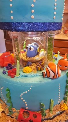 The middle of the Finding Dory cake. The little fish bowl is from Hobby Lobby, I glued a stick up light on the inside of the lid to light up the bowl. The sand was made from pecan cookies and the corral was made of fondant.