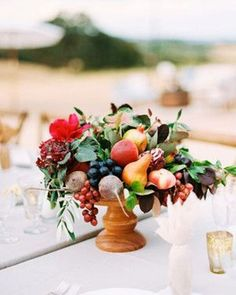 12 Yummy-Looking Wedding Centerpieces With Fruits And Vegetables: a summer centerpiece with grapes, pears, apples and beets and some bold blooms and leaves