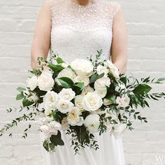 White and green bouquet of roses, ranunculus, ruscus, and salal tips.