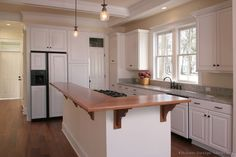 #Kitchen Idea of the Day: Traditional White Kitchen with Wood Bar Top Island