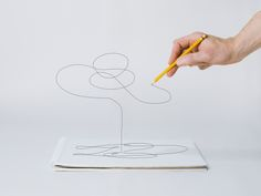 Stock-Foto : Hand with pencil drawing off page